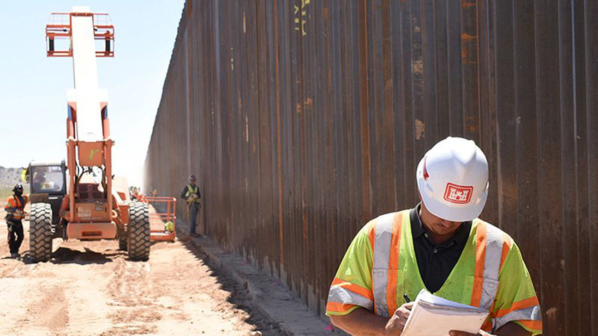 A U.S. Army Corps of Engineers contractor takes notes in May during work on the border wall...