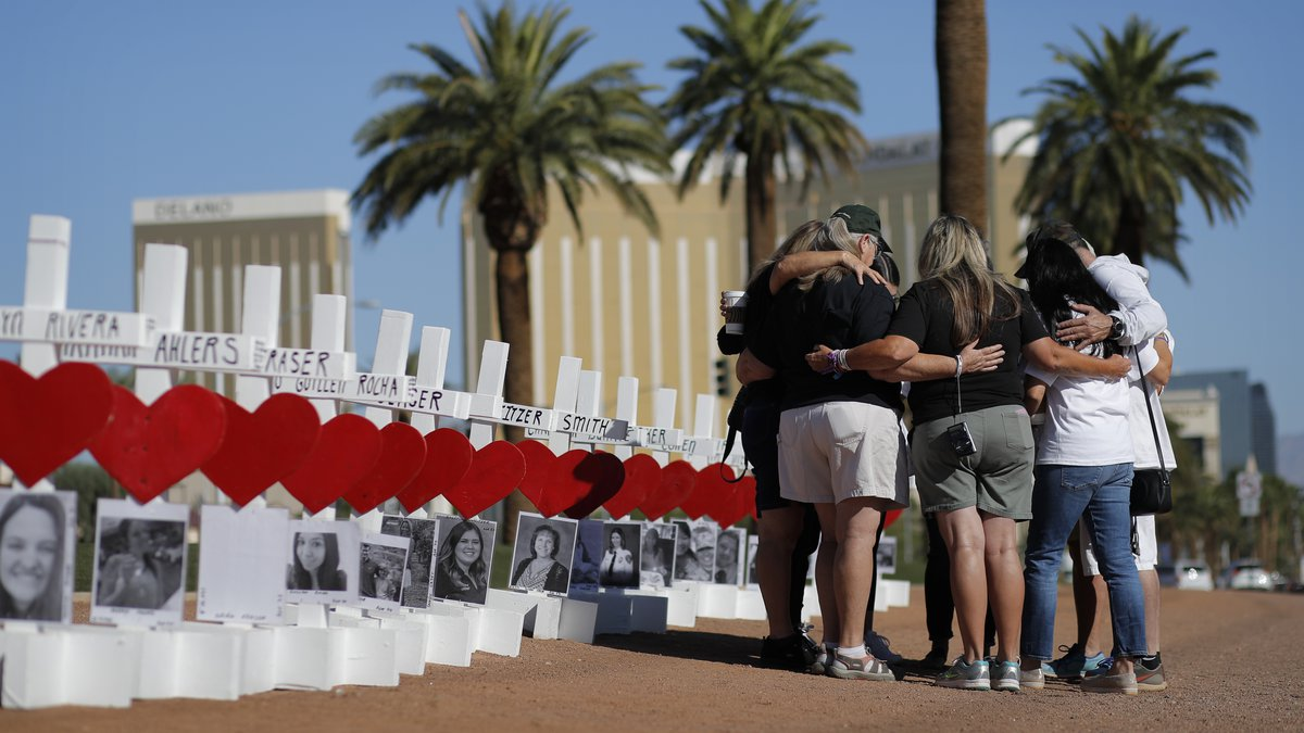 In this Oct. 1, 2019, file photo, people pray at a makeshift memorial for shooting victims in...