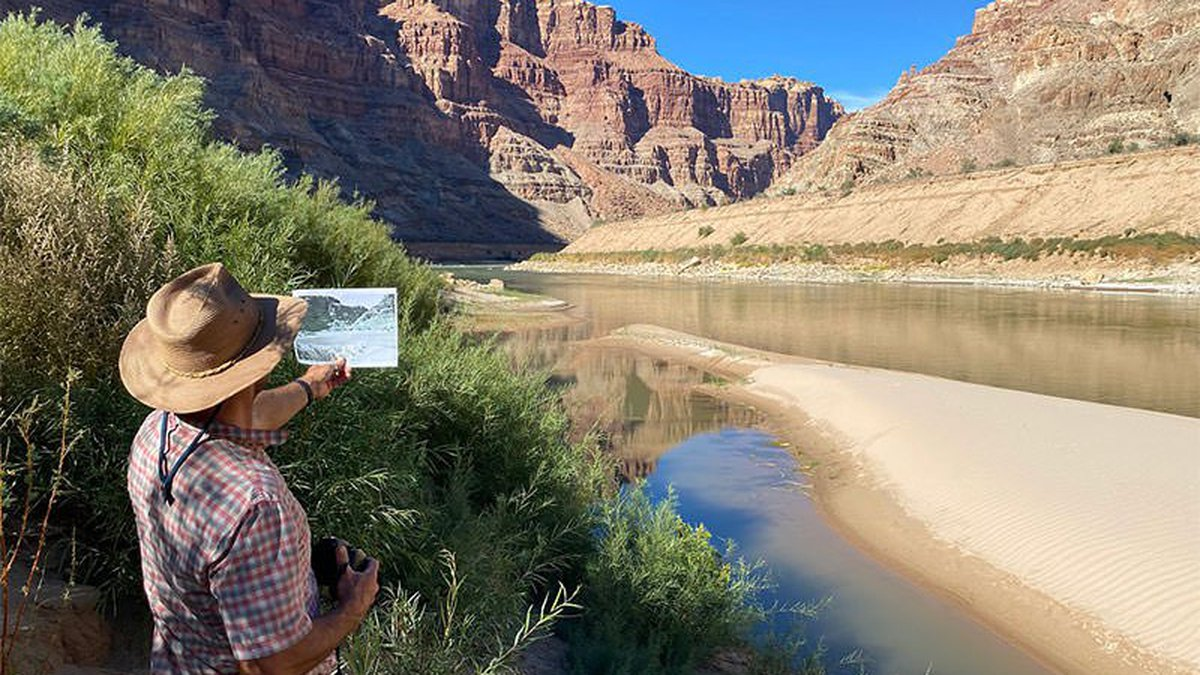 Research scientist Seth Arens compares a historical photo of Cataract Canyon to the present-day...