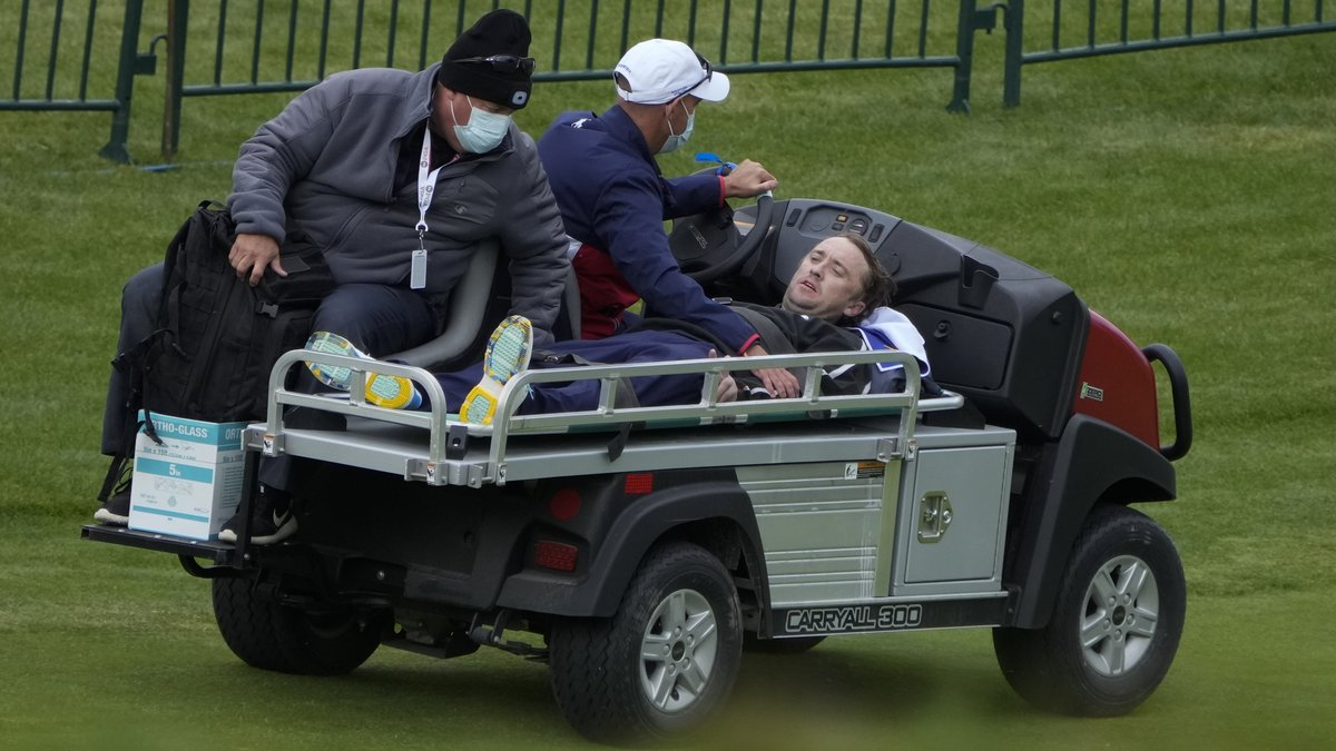 Actor Tom Felton is helped after collapsing on the 18th hole during a practice day at the Ryder...