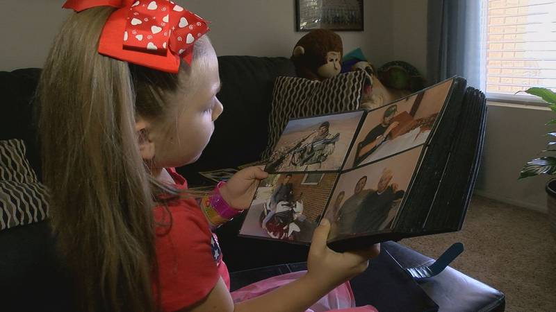 Emily Emriquez, 6, looks through a photo album with pictures of her late dad, Master Sergeant...