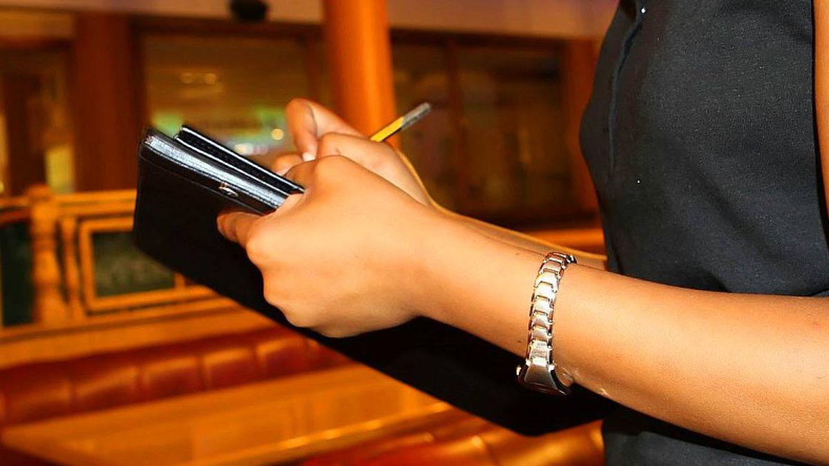 A waitress takes a patron's order at a restaurant.