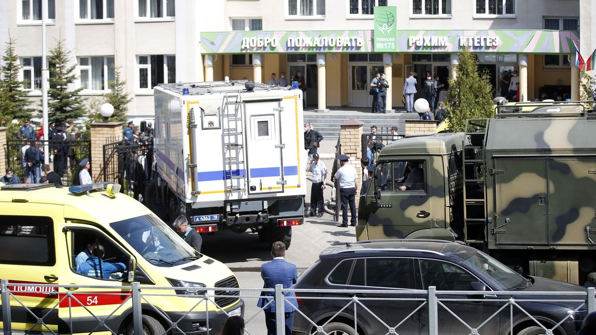 An ambulance and police trucks are parked at a school after a shooting in Kazan, Russia,...