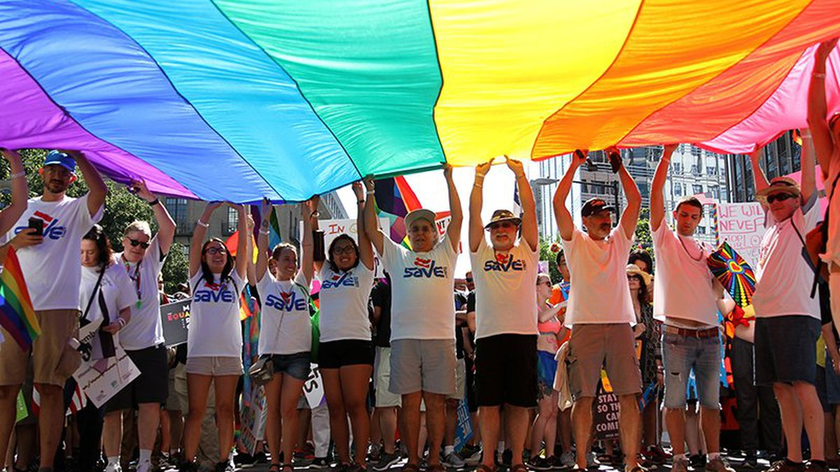 Marchers hoist a rainbow flag in this file photo from a 2017 Equality March in Washington. The...