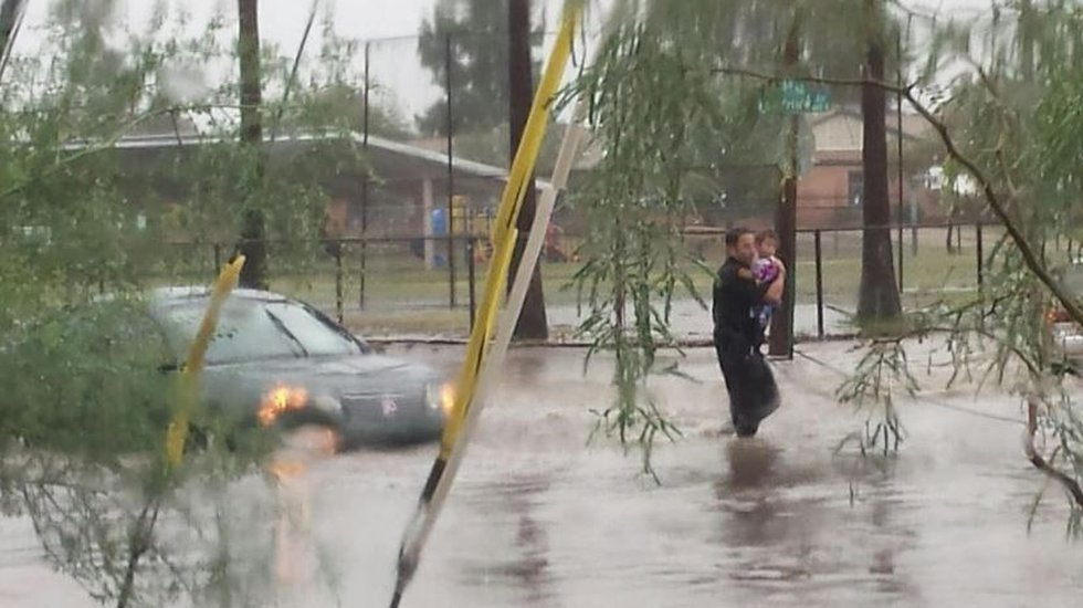 A Tucson Police officer rescues a child from a stranded car in midtown Tucson. (Source:...