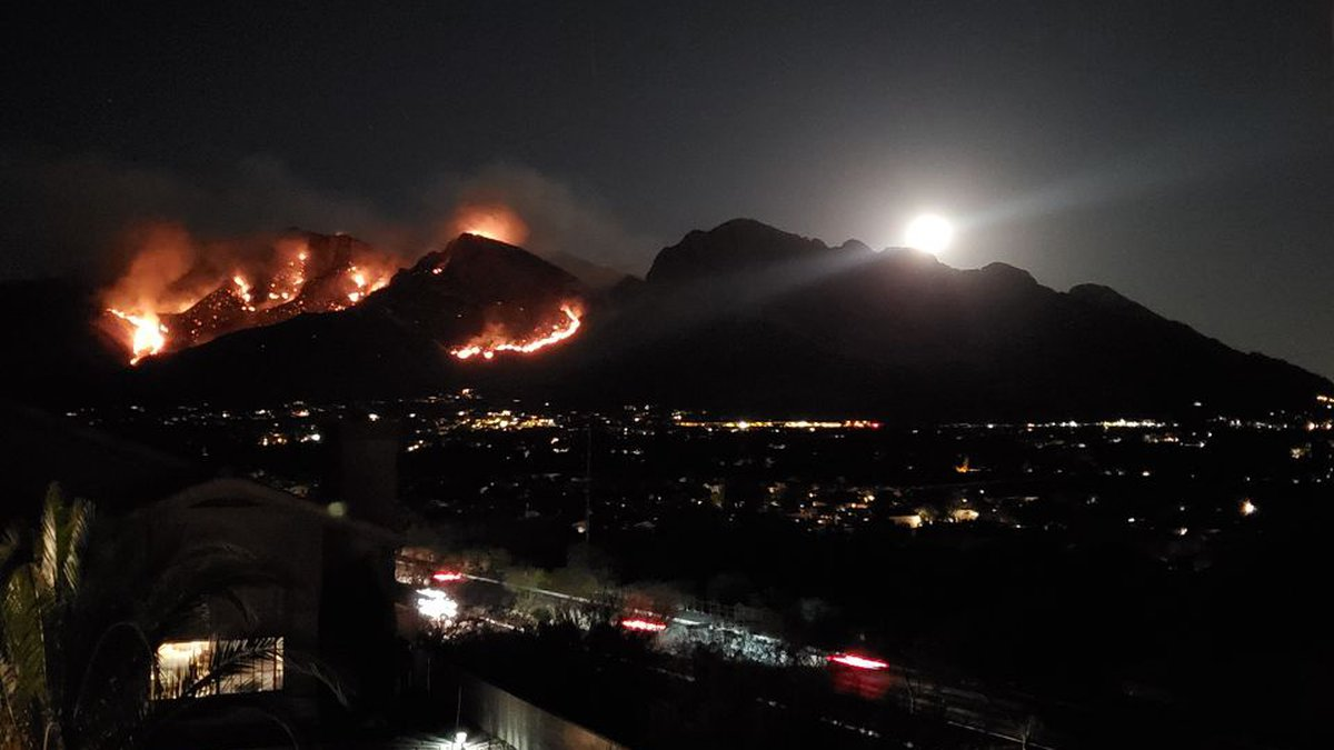 The moon rises over the Bighorn Fire in the Catalina Mountains as seen from Oro Valley on...