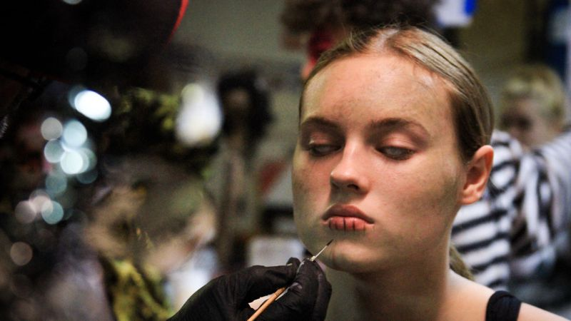 Slaughterhouse makeup artists begin the creepy makeup for the actors in their haunted attraction.