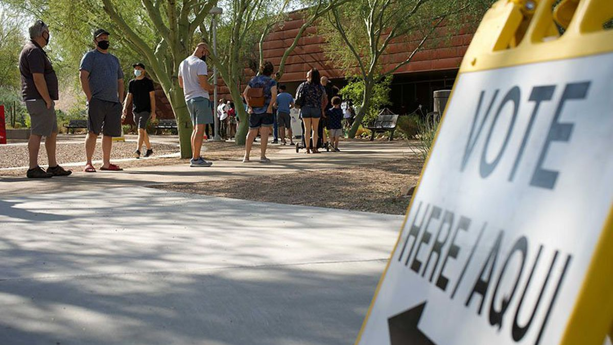 Voters line up outside the Glendale Community College polling center. Despite heavy turnout,...