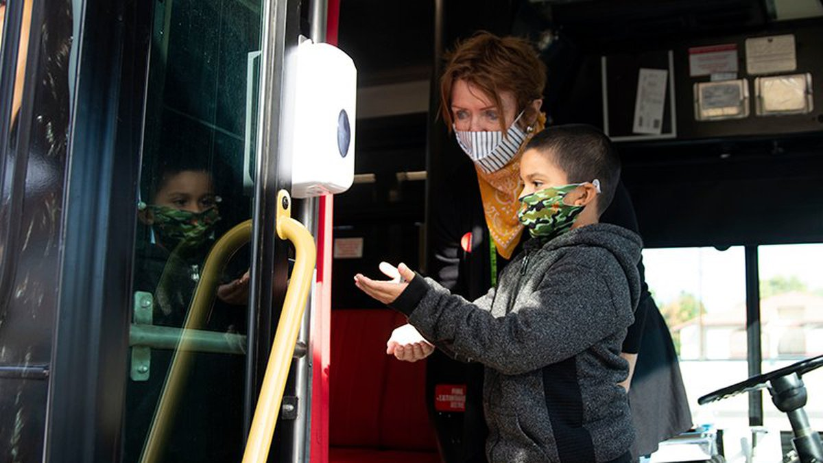Jose Castro, 6, gets help sanitizing his hands from volunteer Pat Medwar during a recent drive...