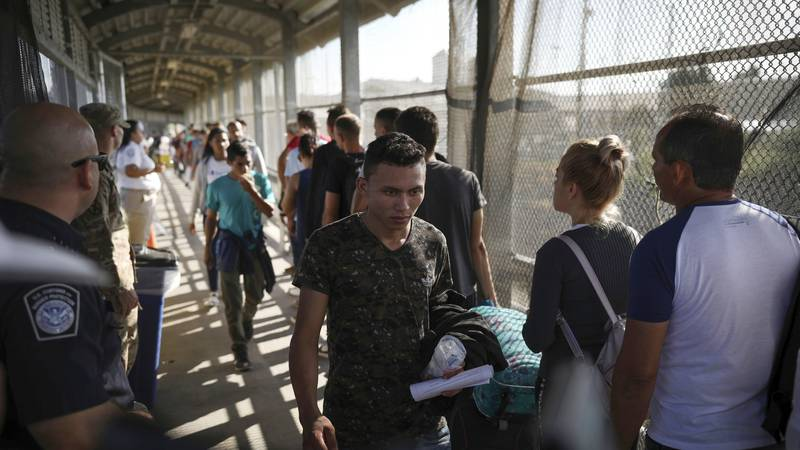 In this Aug. 2, 2019, file photo, migrants return to Mexico as other migrants line up on their...