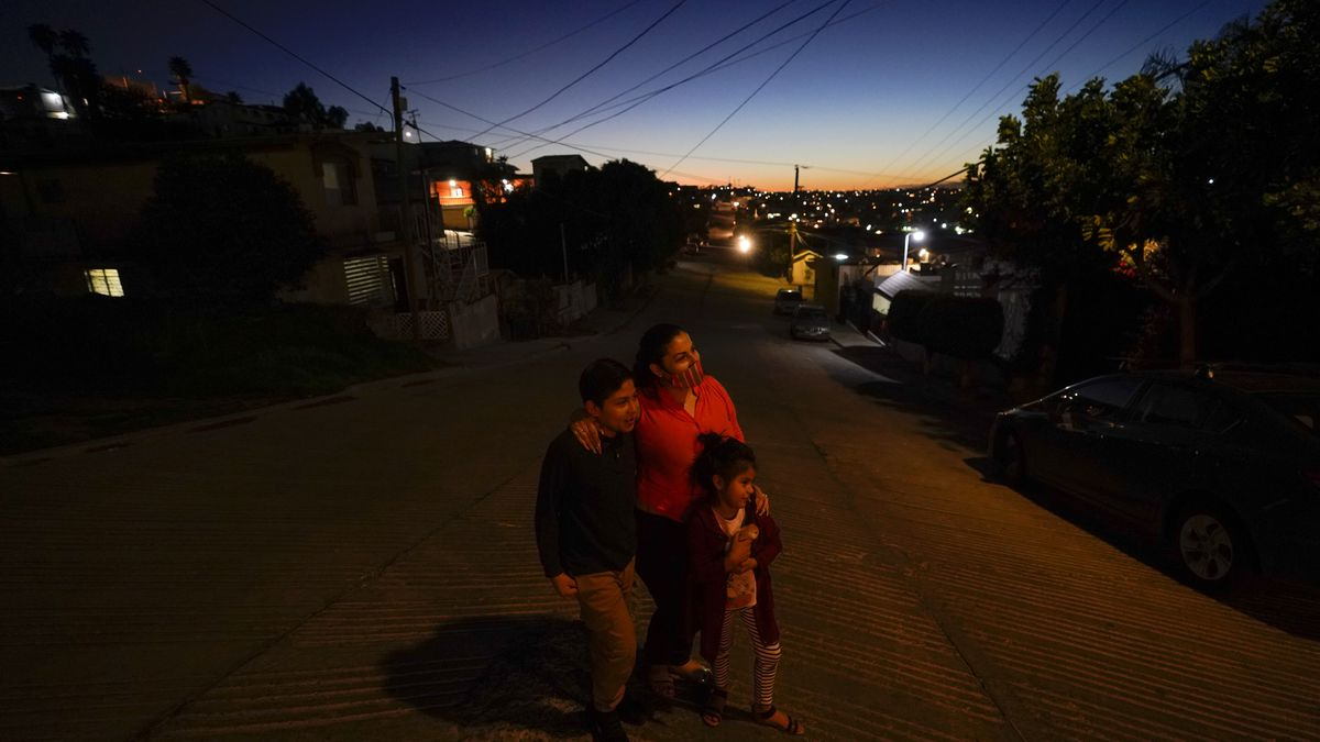 Estela Lazo stands for a portrait with her two children, late Tuesday, Feb. 23, 2021, in...