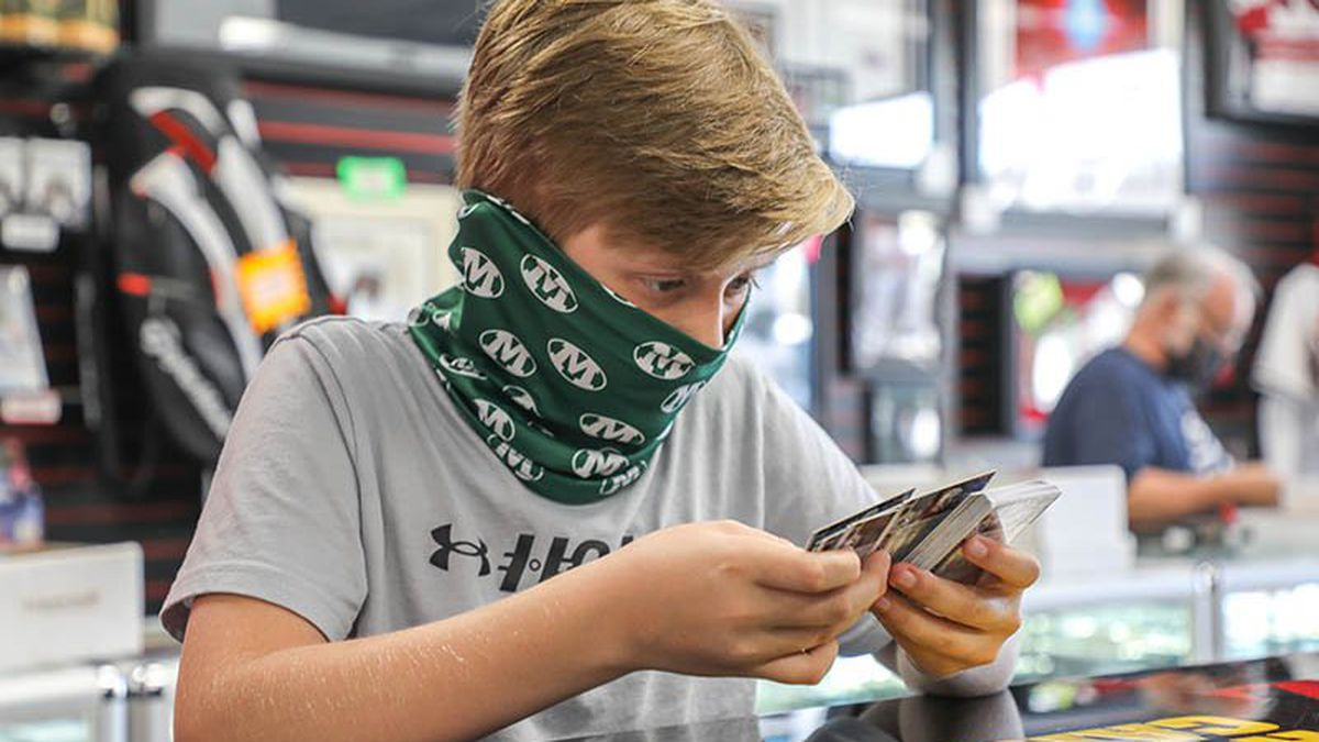 "Danny Grasha, of Medina, Ohio, combs through packets of hockey trading cards looking for ""young..."