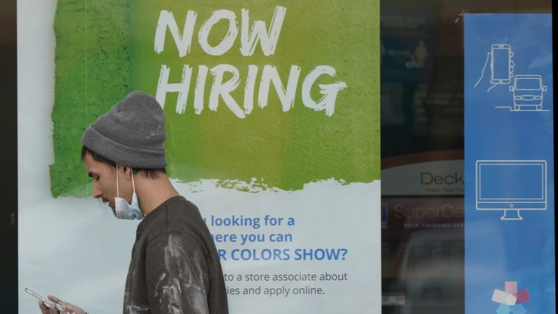 "FILE - A man walks past a ""Now Hiring"" sign on a window at a Sherwin-Williams store, Friday,..."
