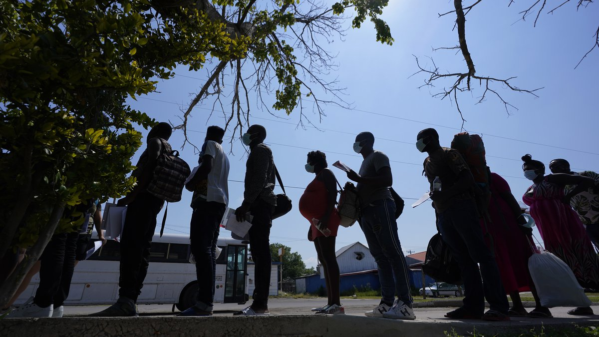 FILE - In this June 16, 2021, file photo migrants stand stand in line at a respite center after...