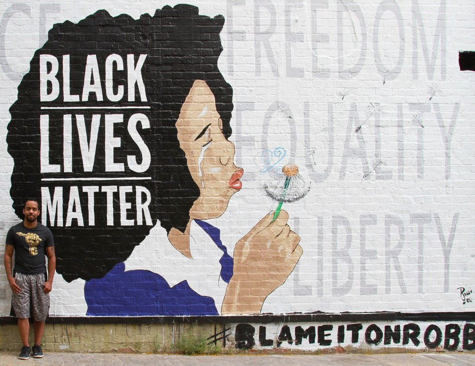 Robbie Lee Harris stands next to his Black Lives Matter mural in Tucson, Ariz. on Friday June...