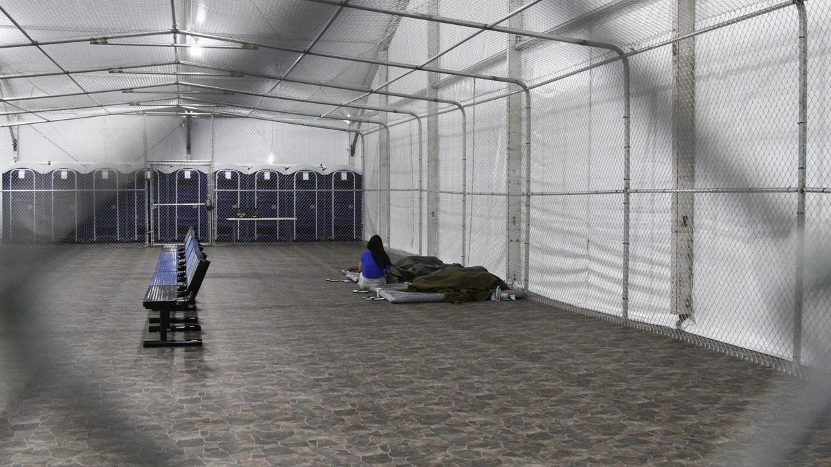 Migrants are detained in a tented, air-conditioned cage at a Border Patrol detention facility...