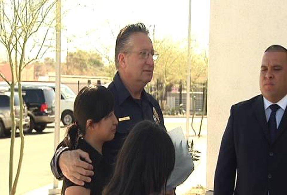 Tucson Fire Captain Fred Bair hugs the woman he saved while Jaime Velasco looks on.