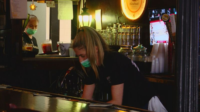 A bartender at Dagwood's Deli and Sports Bar in the Surfside Beach area wears a mask and...