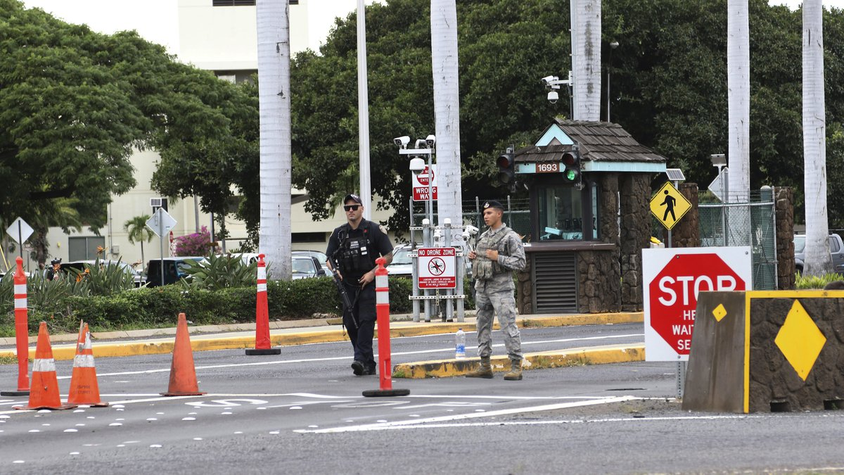 In this Dec. 4, 2019 file photo security stand outside the main gate at Joint Base Pearl...